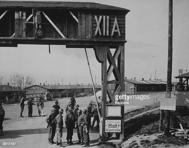 Allied soldiers stand at the entrance to Limburg Prison Camp Germany which was liberated by advancing units of the American 1st Army