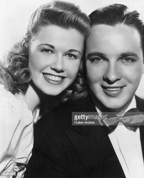 American actor and singer Doris Day and American bandleader Bob Crosby smile while posing forehead to forehead in a promotional headshot portrait...