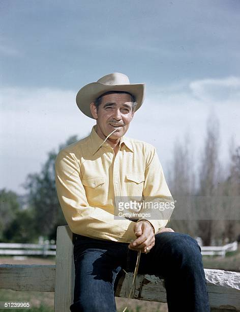 Circa 1945, American actor Clark Gable poses outdoors by a ranch fence, wearing a cowboy hat and chewing a stalk of wheat.