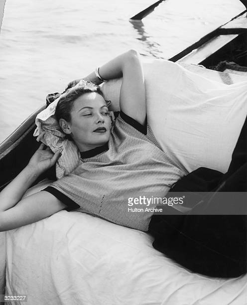 American actor Gene Tierney wearing a striped shortsleeved shirt lounges on a gondola boat Venice Italy