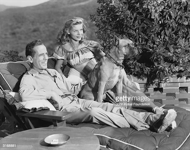 American actor Humphrey Bogart with his wife, Lauren Bacall, and their pet dog.