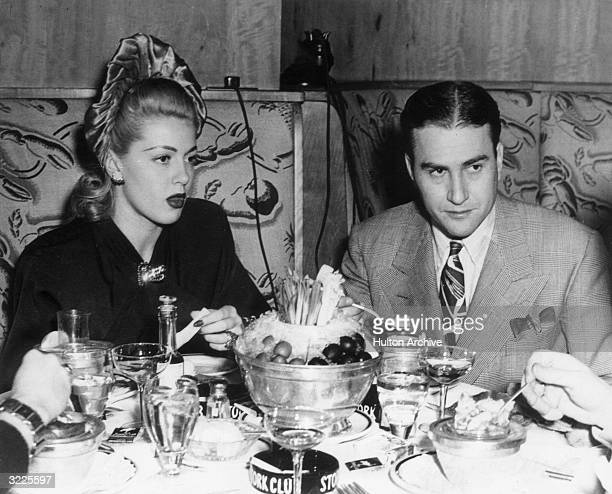 American actor Lana Turner and American bandleader Artie Shaw having a meal while sitting in a booth at a restaurant
