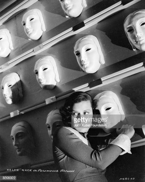 American actress Helen Mack cowers against a wall of identical white masks in a publicity still for one of her films
