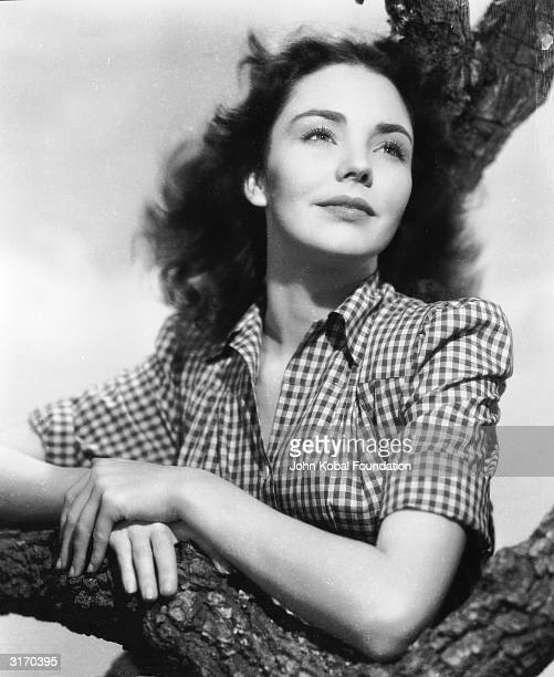 American actress Jennifer Jones leaning against a gnarled tree branch in a checked shirt.