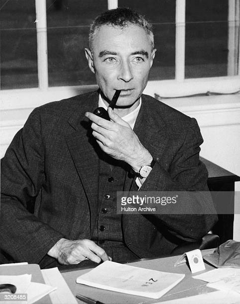 American atomic physicist Dr Robert Oppenheimer sits behind a desk smoking a pipe with a book entitled 'Zen' in front of him