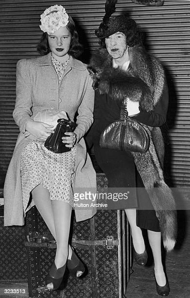 American heiress Gloria Vanderbilt and her aunt Gertrude Vanderbilt Whitney sit on top of a Louis Vuitton trunk after returning from a cruise