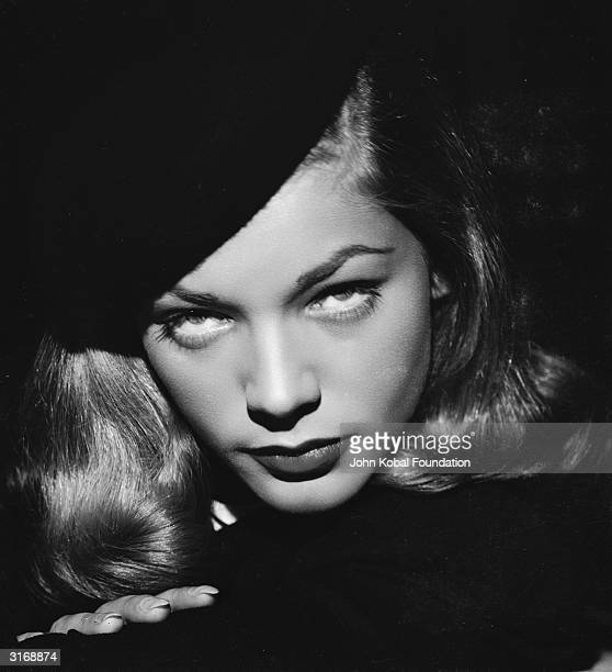 American screen star Lauren Bacall glowers over her shoulder
