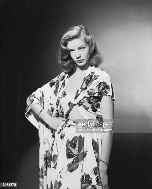 American screen star Lauren Bacall wearing a summer suit in a bold floral print