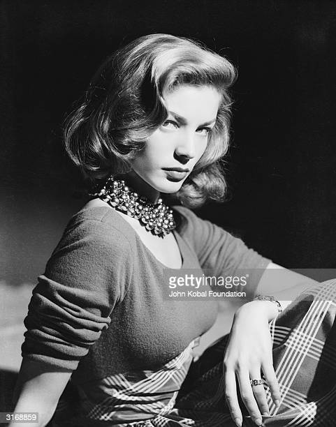 American screen star Lauren Bacall wearing an ornate beaded necklace