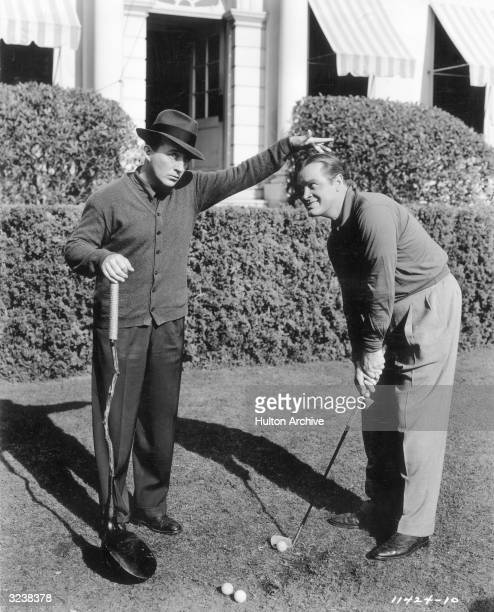 American singer and actor Bing Crosby holds an unusually large golf club and places his hand on top of the head of Britishborn entertainer Bob Hope