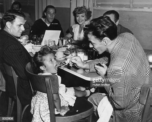 American singer Frank Sinatra feeds his daughter Nancy while seated at a table with actors Gene Kelly and Pamela Britton in the MGM commissary Culver...