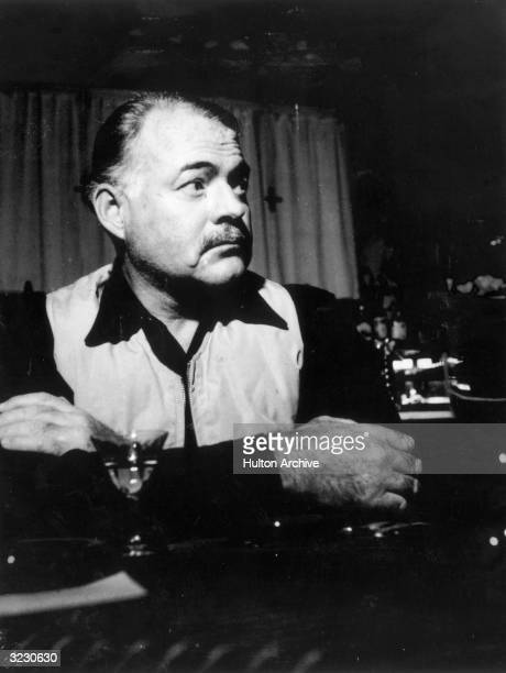 American writer Ernest Hemingway sits at a bar with a cocktail.