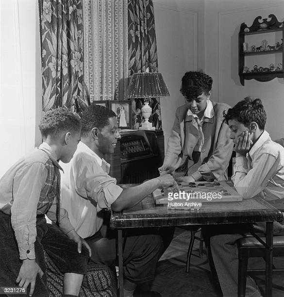 An AfricanAmerican father plays checkers with his son in his living room while his other son and daughter look on