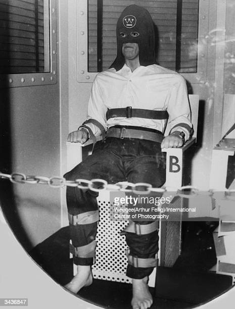 An American prisoner sentenced to death is strapped into a chair in the gas chamber The black hood carries a Westinghouse Electric Company logo Photo...