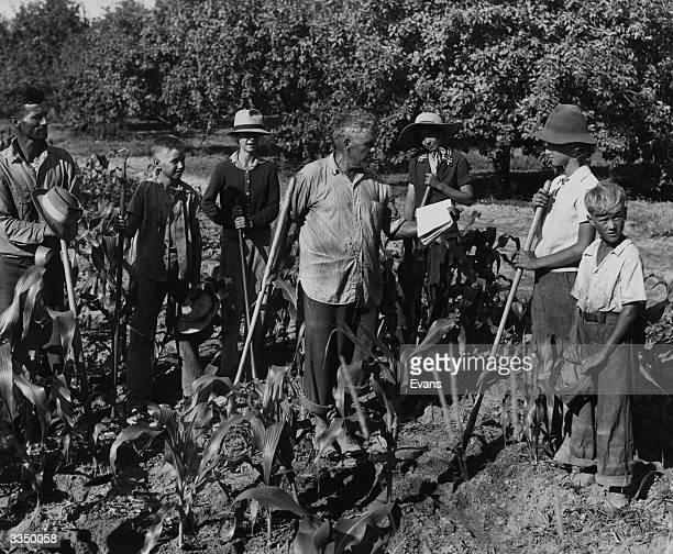 An elderly farmers reads instructions to a group of helpers who are ready with their hoes on his farm in Tennessee USA