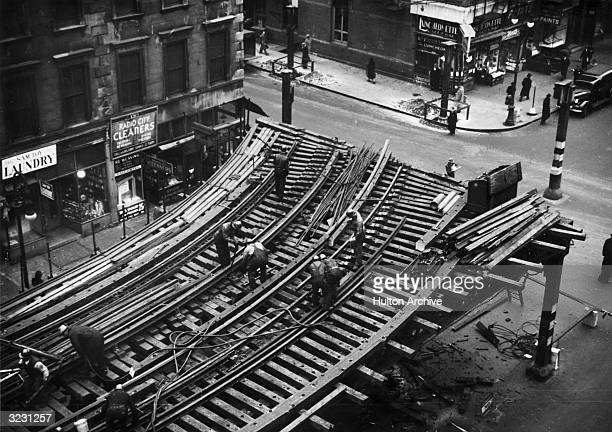 An overhead view of transit workers standing atop the Sixth Avenue elevated train tracks, working to dismantle the railway at Sixth Avenue and 53rd...
