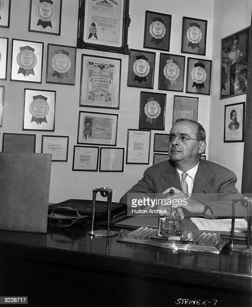Austrian composer Max Steiner smoking a cigar while sitting behind a desk surrounded by framed awards and letters.