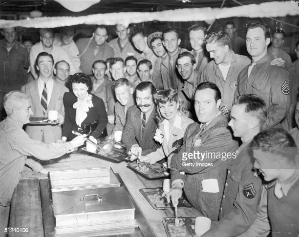 Circa 1945, Bob Hope , Frances Langford and Jerry Colonna stand in the meal line in a mess hall as US soldiers look on during a USO function.