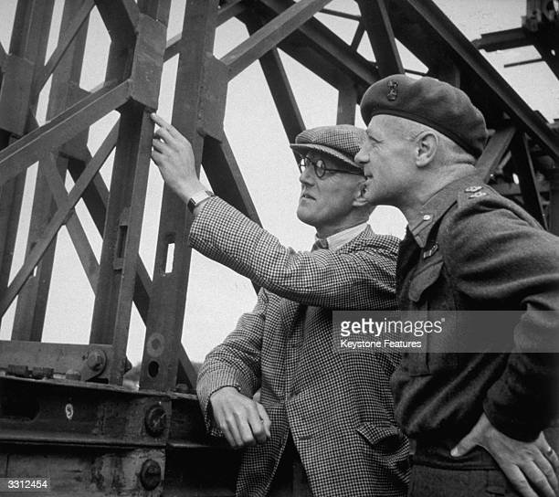 British engineer Sir Donald Bailey who designed the prefabricated mobile rapidlyerected bridge seen here explaining the joint of a span to a British...