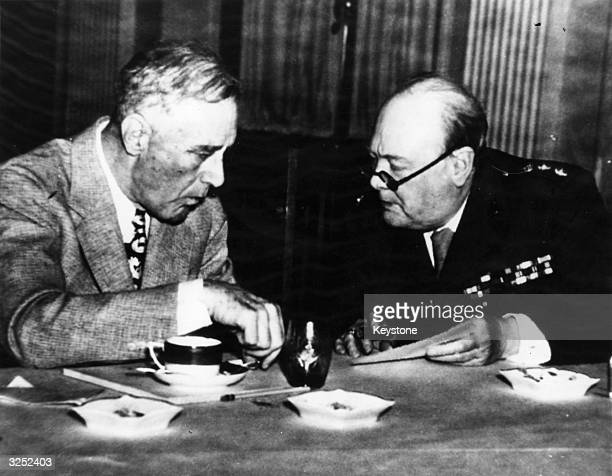 British Prime Minister Winston Leonard Spencer Churchill discusses tactics with the statesman and 32nd American President Franklin Delano Roosevelt...