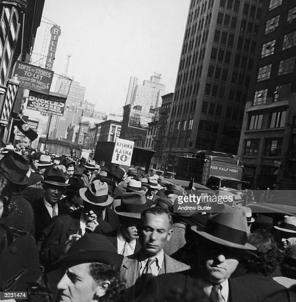 Canted view of a crowd of people walking on Seventh Avenue near W 40th Street in the Garment Center New York City