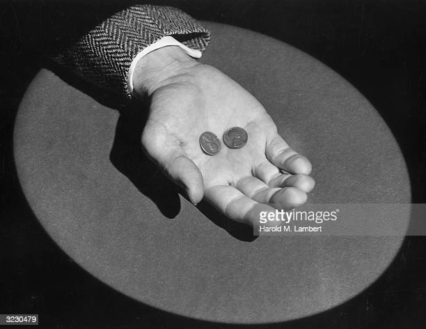 Closeup of a man holding two pennies in his palm illuminated by a spotlight