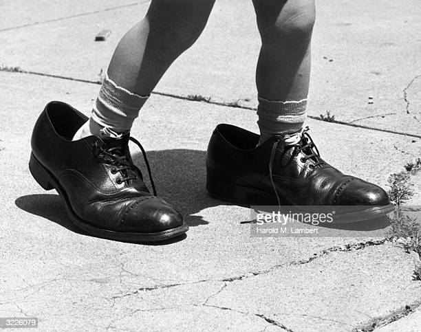 Closeup of the feet of a young child seen from the knee down wearing a pair of men's shoes on a sidewalk