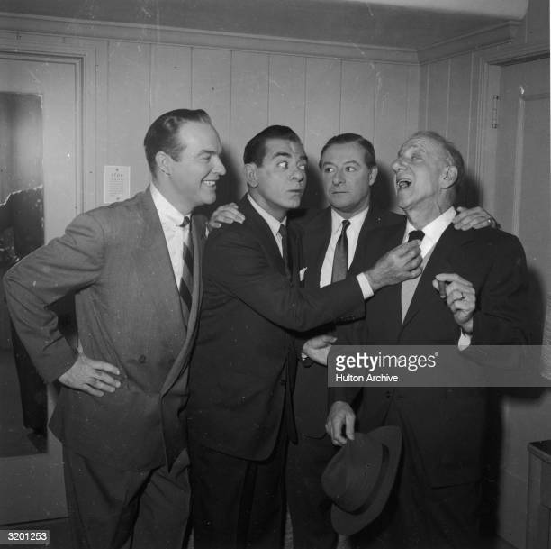 Comedian Jimmy Durante sings while actor Eddie Cantor adjusts Durante's tie and radio announcer Ralph Edwards and actor George Jessel look on