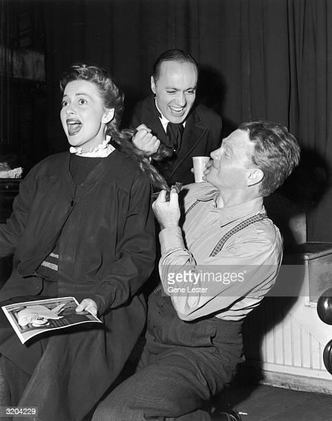 EXCLUSIVE Actors Charles Boyer and James Cagney smile as they pull actor Olivia De Havilland's braids during a stop with the Hollywood Victory...