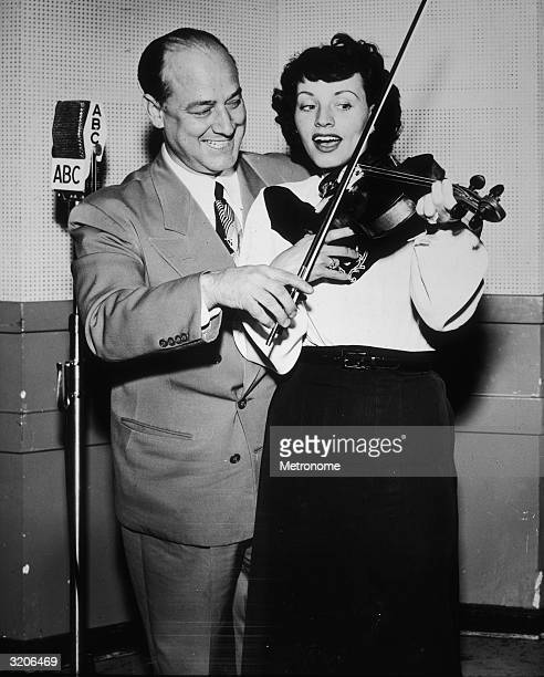 American jazz violinist Joe Venuti and American vocalist Kay Starr smile and sing while playing a violin together. They stand by an ABC microphone.
