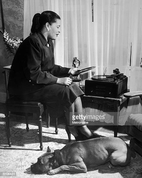 EXCLUSIVE American jazz vocalist Billie Holiday sitting by a window and holding a record with a dog lying at her feet