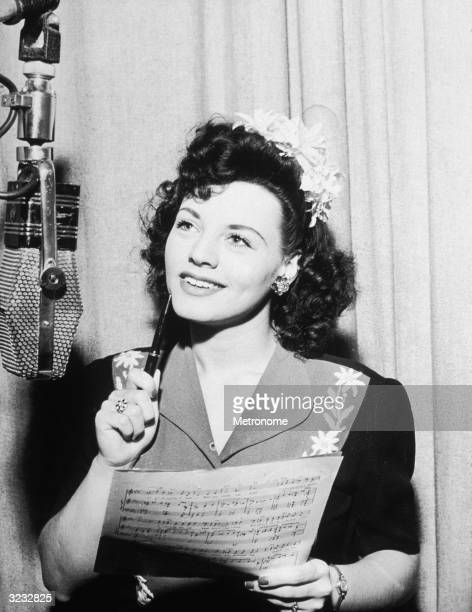 American singer Kay Starr, looking up at an overhead microphone, holding sheet music and pressing a pen to her chin.