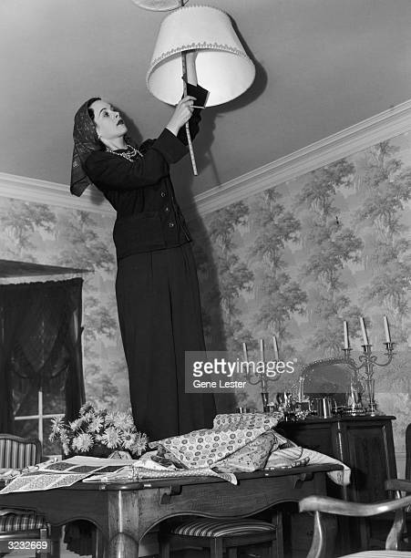 EXCLUSIVE Austrianborn actor Hedy Lamarr standing on her dining room table and measuring a lamp shade Lamarr who is wearing a kerchief around her...
