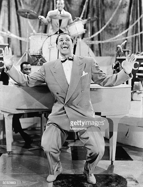 EXCLUSIVE Fulllength image of American jazz singer and bandleader Cab Calloway crouching with his hands in the air while performing in front of a...