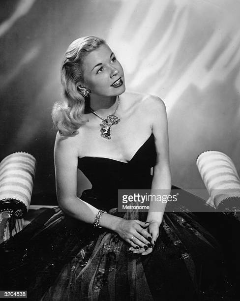 EXCLUSIVE Portrait of American actor and singer Doris Day sitting on a divan and wearing a fullskirted evening gown with a jeweled pendant