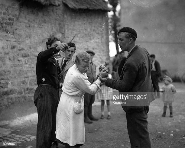 French patriots crop the hair of a woman they suspect of collaborating with the Germans during the occupation