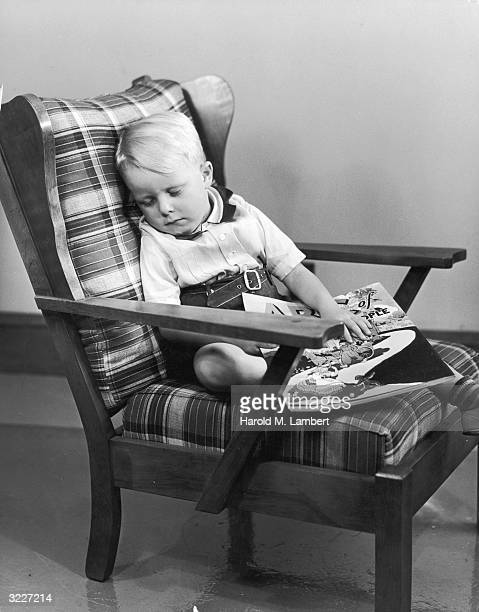 Fulllength image of a young boy sitting asleep in a plaid upholstered hair with his hand on a large comic book