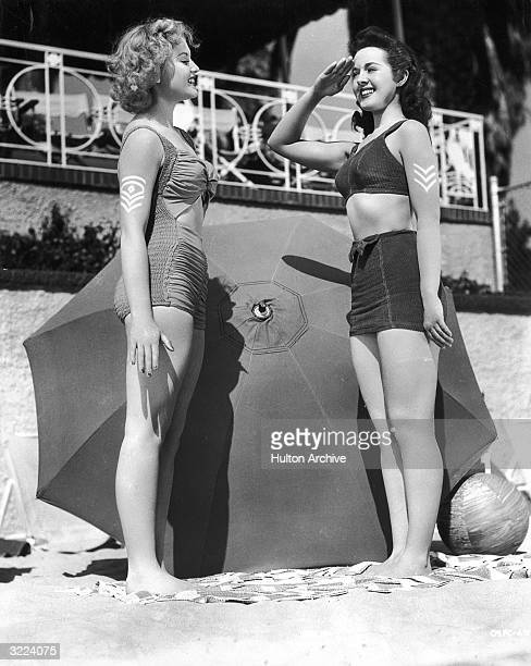 Full-length image of actors Elaine Morey and Peggy Moran wearing military sun tattoos on their arms.