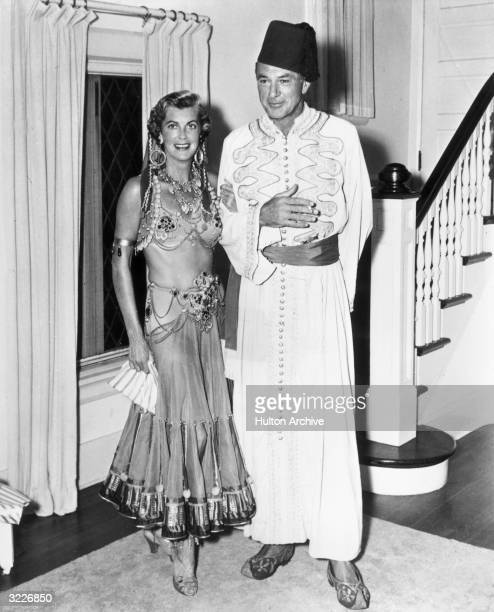 Full-length image of American actor Gary Cooper posing with his wife, Sandra Shaw 'Rocky' , wearing Middle Eastern costumes. Cooper wears a fez, a...