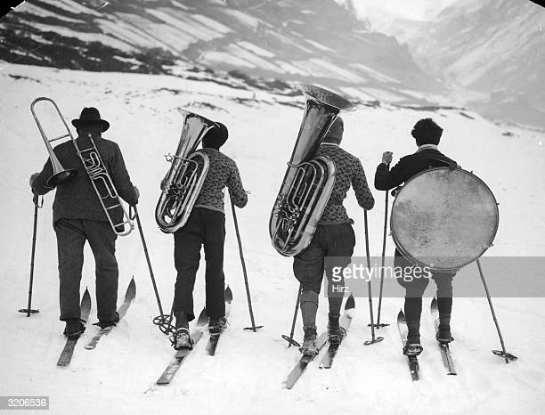 Fulllength image of four musicians wearing crosscountry skis while toting their instruments on their backs through a snowy mountain range They carry...