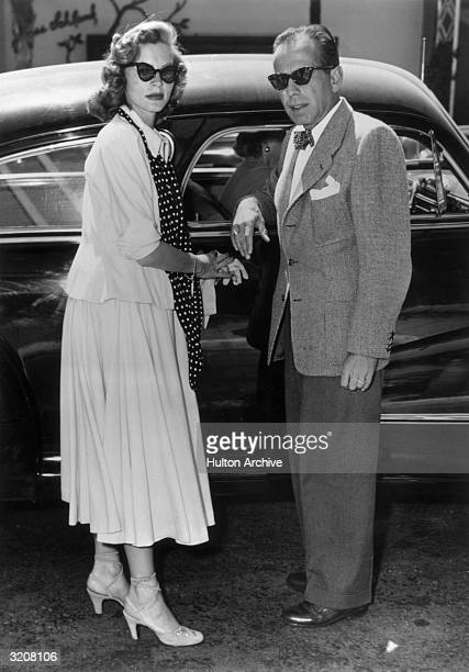 Fulllength image of married American actors Lauren Bacall and Humphrey Bogart standing by an automobile They wear sunglasses