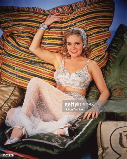Fulllength portrait of American actor and singer Alice Faye leaning back against a large cushion while wearing a beaded haremstyle costume with a...