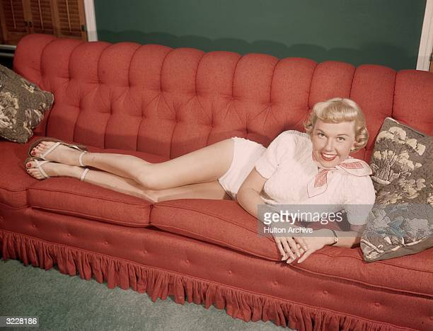 Fulllength portrait of American actor Doris Day reclining on a red couch and smiling Day is wearing a white leotard and a red and white scarf