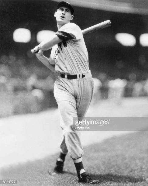Fulllength portrait of American baseball player Ted Williams outfielder and slugger for the Boston Red Sox holding the followthrough of his swing...