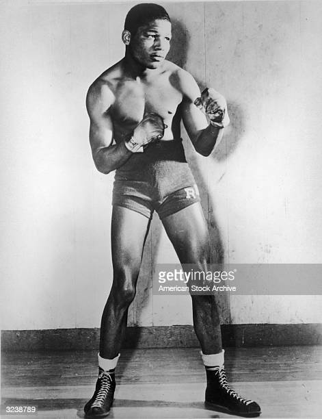 Fulllength portrait of American boxer Sugar Ray Robinson posing in a fighting stance with boxing gloves and trunks