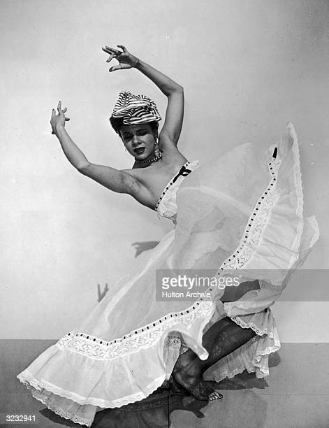 Fulllength portrait of American dancer and choreographer Katherine Dunham bending her knees and holding her hands above her head in an...