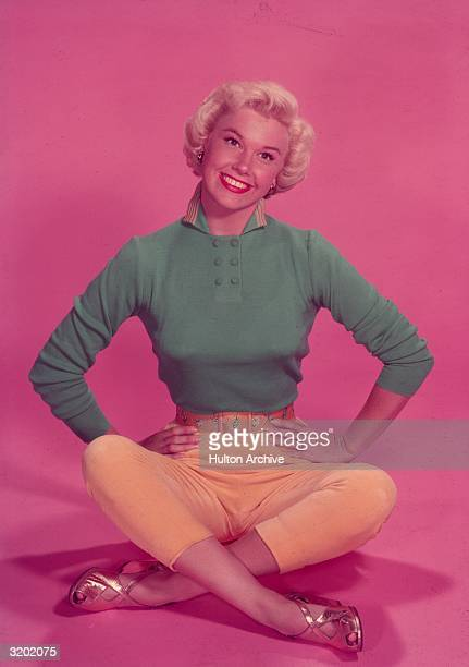 Fulllength studio portrait of American actor and singer Doris Day sitting on the floor in front of a pink backdrop her legs crossed and her hands on...