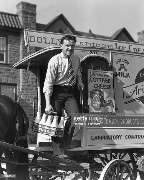 Fulllength view of a milkman stepping off the side of his horsedrawn truck to deliver a crate of milk Philadelphia Pennsylvania