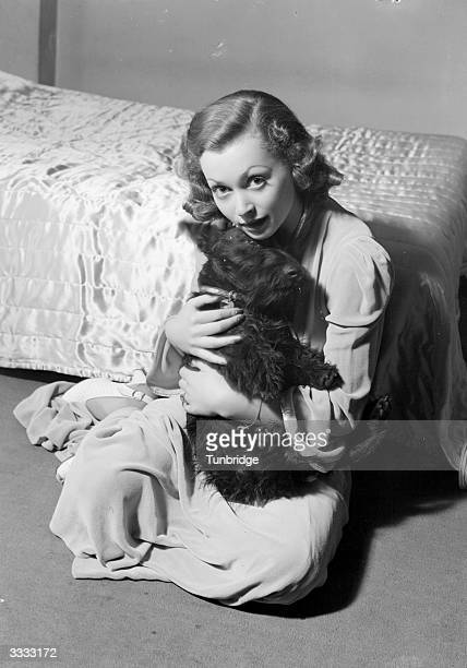 German actress and author Lilli Palmer cuddling a pet dog at home.