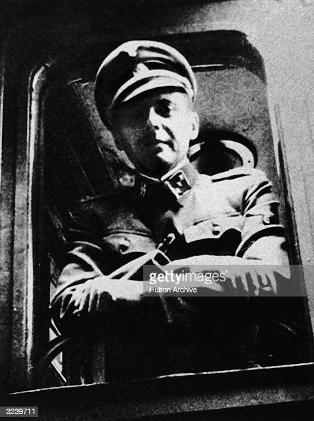 German Nazi doctor and war criminal Josef Mengele standing at a train window his SS uniform.